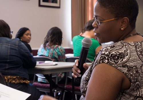 Participants in class, learning, taking notes, and asking questions. Most students are dark skinned. The woman nearest to camera is speaking into a mic, as if asking a question or participating in class using a mic.