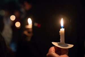 image of hand holding lit candle, other candles held similarly nearby